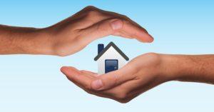 Hände halten schützend über ein Haus